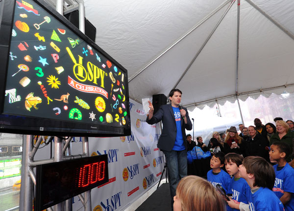 Kevin Duda explains the rules to young participants in I SPY's 20th Anniversary Celebration in Times Square