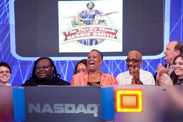 Miche Braden (center) rings the closing bell at NASDAQ