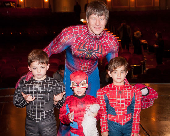 An unmasked Christopher Tierney with kids in Spider-Man costumes