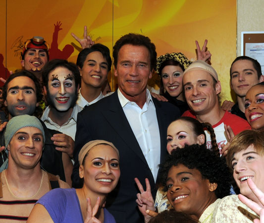 Arnold Schwarzenegger with cast members from Cirque du Soleil's The Beatles LOVE