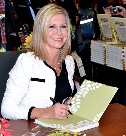 Olivia Newton-John signs a copy of Livwise