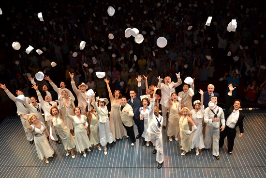 The company of Anything Goes and the audience toss their sailor hats in the air