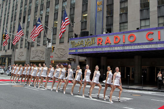 "The Rockettes perform at the annual ""Christmas in August"" event on 6th Avenue in front of Radio City Music Hall
