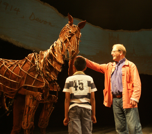 Author Michael Morpurgo and Joey from War Horse meet a child during a Kids Week Q&A at the New London Theatre