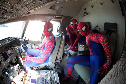 Three costumed cast members from the musical Spider-Man Turn Off the Dark check out the cockpit of an American Airlines plane